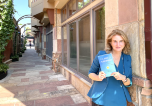 patty holding book outside
